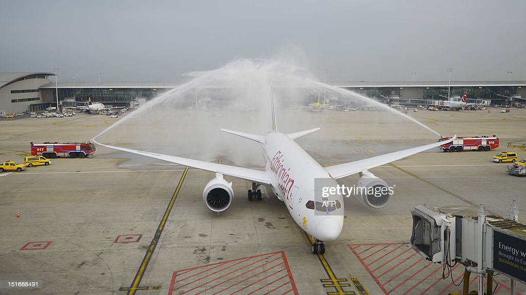Fire engines spray water over an Ethiopian Airlines' Boeing 787 Dreamliner aircraft parked at Brussels airport for the first time on September 10, 2012, in Zaventem. Ethiopian Airlines, the first African company to have bought this aircraft, purchased ten Dreamliners. Built largely with lightweight composite materials, Boeing says the Dreamliner is about 20 percent more fuel efficient than similarly sized aircraft and is the first mid-size airplane capable of flying long-range routes. AFP PHOTO / BELGA / ERIC LALMAND