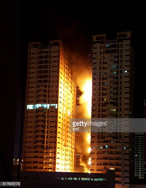 Fire engulfs a tower at a residential cluster in Ajman in the United Arab Emirates March 28 2016 The fire erupted at a building in the Ajman One...
