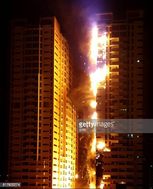 TOPSHOT Fire engulfs a tower at a residential cluster in Ajman in the United Arab Emirates March 28 2016 The fire erupted at a building in the Ajman...