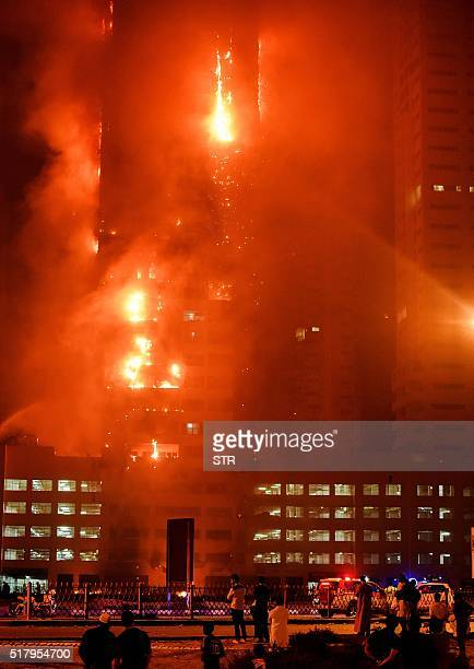 Fire engulfs a tower at a residential cluster in the northern UAE emirate of Ajman early on March 29 2016 The fire erupted at a building in the Ajman...