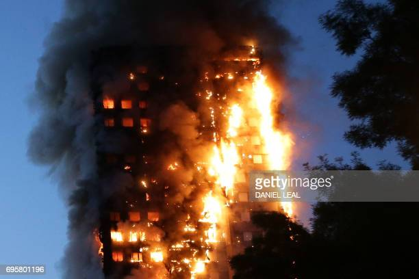 TOPSHOT Fire engulfs Grenfell Tower a residential tower block on June 14 2017 in west London The massive fire ripped through the 27storey apartment...