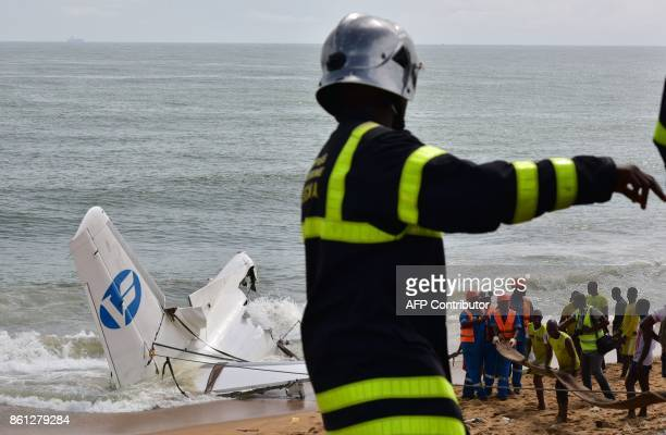 A fire fighter gestures as rescuers try to pull out the wreckage of a cargo plane that crashed off Ivory Coast killing four on the beach of PortBouet...