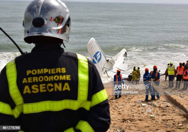 A fire fighter stands as rescuers try to pull out the wreckage of a cargo plane that crashed off Ivory Coast killing four on the beach of PortBouet...
