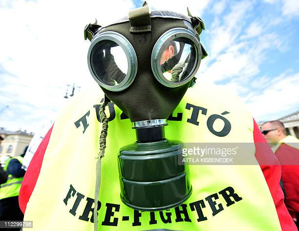 A fire fighter wears a gasmask on his back as thousands of participants including policemen fire fighters soldiers and prison guards marched in...