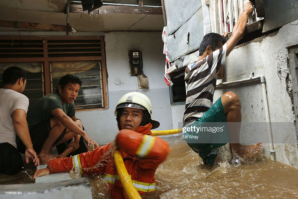 Fire fighters and neighborhood residents struggle to move a firehose into position to put out a fire in a flooded neighborhood on January 18, 2013 in Jakarta, Indonesia. According to the National Disaster Management Agency, about 50 percent of the capital is under water following the floods which have so far claimed eleven lives and displaced thousands of Indonesians.