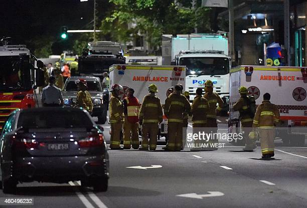 Fire fighters and paramedics wait as armed police carry out an operation outside the cafe where a gunman had taken people captive in the central...
