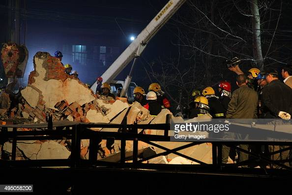 Fire fighters and rescuers search for trapped construction workers after a reconstructed house collapsed on Friday afternoon in Wuyang County on...