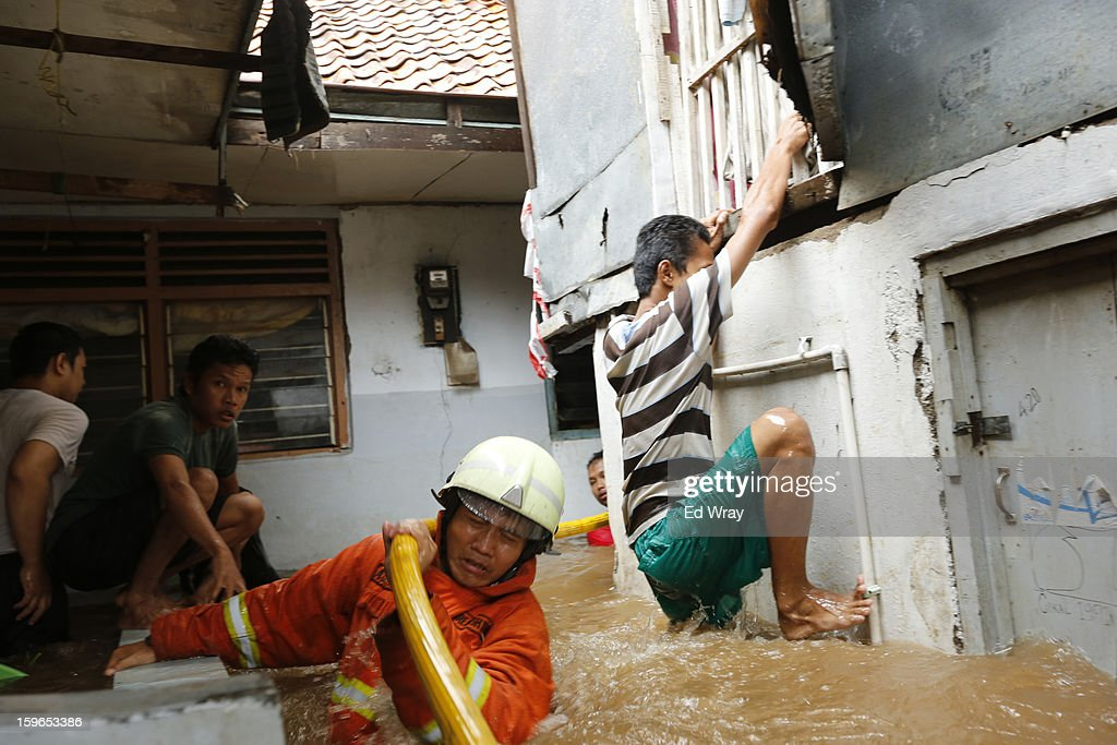 Fire fighters and residents struggle to move a firehose into position to put out a fire in a flooded neighborhood on January 18, 2013 in Jakarta, Indonesia. According to the National Disaster Management Agency, about 50 percent of the capital is under water following the floods which have so far claimed eleven lives and displaced thousands of Indonesians.