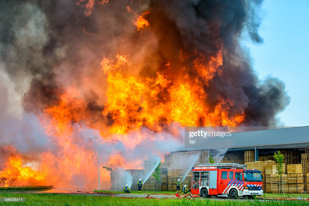Fire fighters at an industrial inferno : Stock Photo