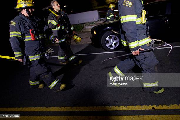 Fire fighters carry tools back to their truck in the early hours after working at the wreckage of an Amtrak passenger train that derailed carrying...