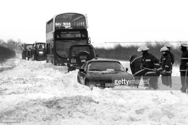 Fire Fighters dig out a bus and cars trapped in blizzards and drifting snow near Market Weighton Yorkshire Friday December 30 as the UK braces itself...