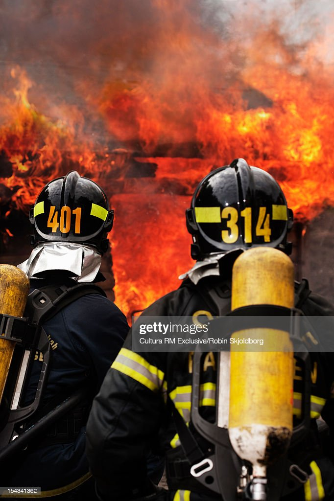 Fire fighters examining blaze : Stock Photo
