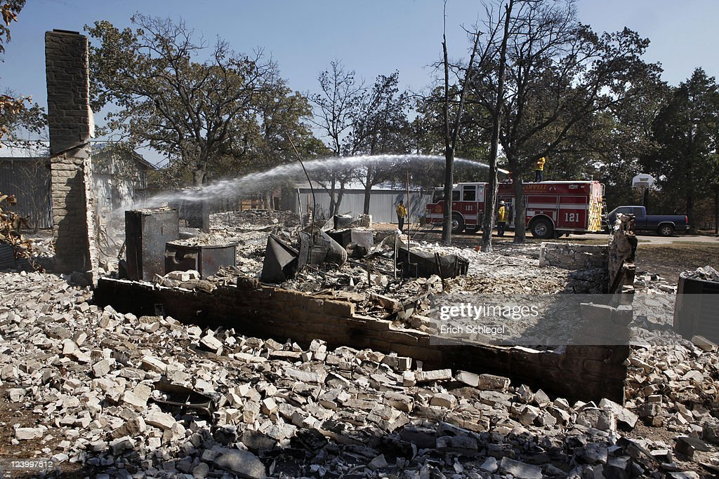 Fire fighters from the Coppell Fire Department hit hot spots on a burned down house with water as they go to the wildfire-affected areas September 7, 2011 in Bastrop, Texas. Several large wildfires have been devastating Bastrop County for the last three days, but are now 30 percent contained, according to the Texas Forest Service.