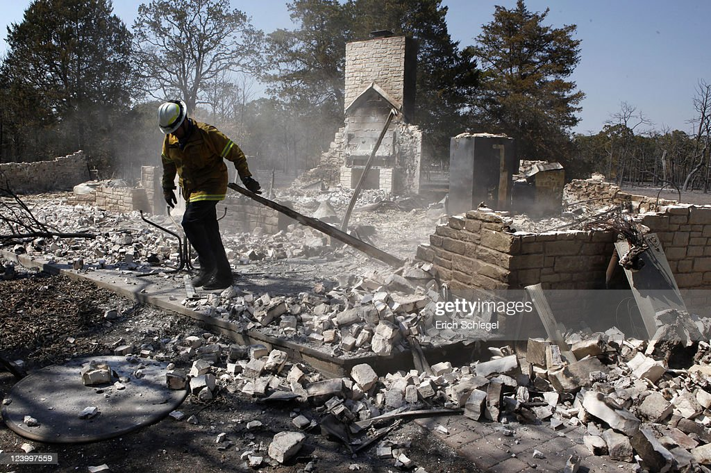 Fire fighters from the Coppell Fire Department prepare to hit a burned down house with water as they go to the wildfire-affected areas September 7, 2011 in Bastrop, Texas. Several large wildfires have been devastating Bastrop County for the last three days, but are now 30 percent contained, according to the Texas Forest Service.