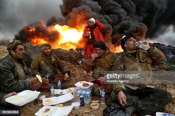 Fire fighters give a break during trying to extinguish the fire at oil wells were set on fire by Daesh terrorists as they fled after Al Qayyarah...