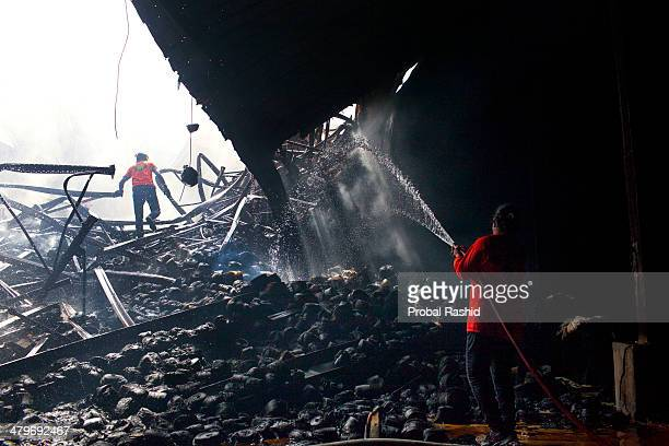 Fire fighters hose smouldering remains after a devastating fire at the dyeing section of the twostorey Aswad Composite Mills at Maona Gazipur At...