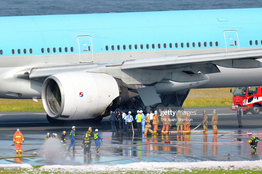 fire fighters investigate the cause of a fire from an engine on the left side of the Korean Air 2708 bound for Seoul at the Haneda International Airport on May 27, 2016 in Tokyo, Japan. 319 passengers and crews have safely evacuated. C runway has been closed.
