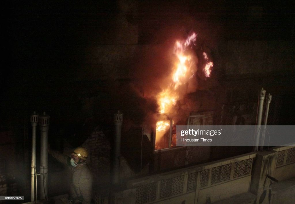 Fire fighters looks on as flames of fire goes off at a godown in Bhagirath Palace, an electrical market of Chandni Chowk area, on December 13, 2012 in New Delhi, India. The blaze erupted at Bhagirath Palace market at around 5.10 pm and 22 fire tenders were immediately rushed to the spot. The fire is doused with no casualties reported.