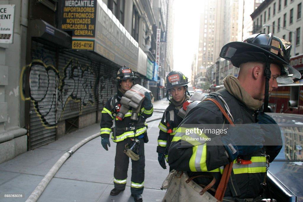 Fire fighters respond to a call inside a building in Chelsea While their buddies are inside the others wait in full gear with fire hoses on their...