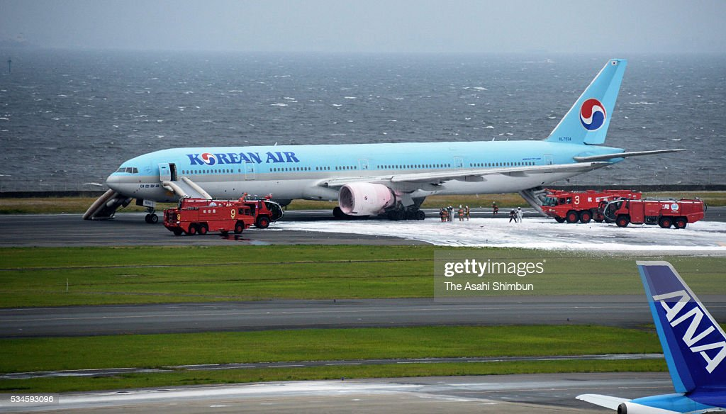 Fire fighters spray foam to an engine on the left side of the Korean Air 2708 bound for Seoul at the Haneda International Airport on May 27, 2016 in Tokyo, Japan. 319 passengers and crews have safely evacuated. C runway has been closed.