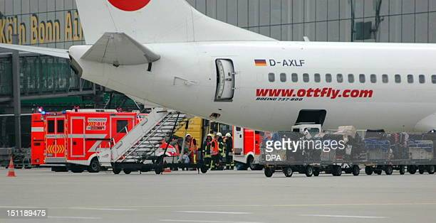 Fire fighters stand next to a Turkeybound jet at Cologne/Bonn airport near Cologne western Germany on September 3 2012 Eleven passengers required...