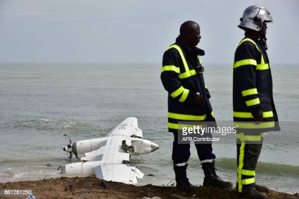 Fire fighters stand on the beach of PortBouet in Abidjan near the wreckage of a cargo plane that crashed off Ivory Coast killing four on October 14...