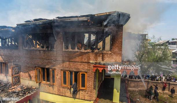Fire fighters try to douse a residential house engulfed in flames on APRIL 18 2017 in Srinagar the summer capital of Indian administered Kashmir...