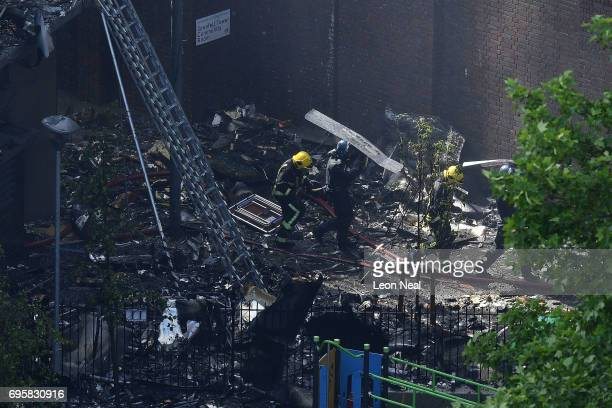 Fire fighters use a riot shield as protection from falling rubble at the 24 storey residential Grenfell Tower block in Latimer Road West London in...