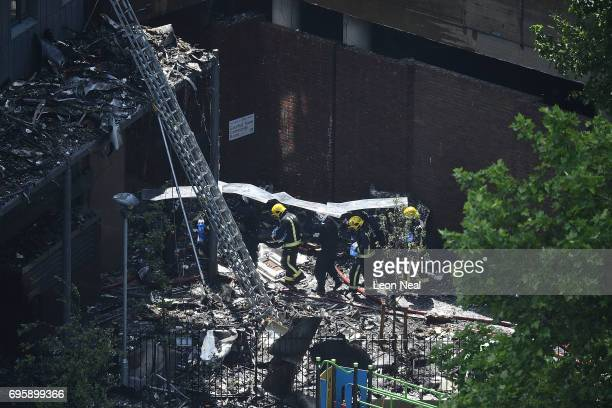 Fire fighters use a riot shield as protection from falling rubble at the burning 24 storey residential Grenfell Tower block in Latimer Road West...