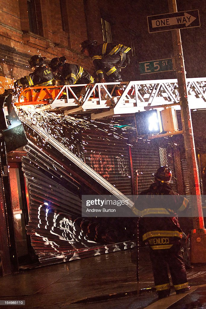 Fire fighters use a saw in an attempt to remove a partially collapsed door due to Hurricane Sandy on October 29, 2012 in New York, United States. Hurricane Sandy, which threatens 50 million people in the eastern third of the U.S., is expected to bring days of rain, high winds and possibly heavy snow. New York Governor Andrew Cuomo announced the closure of all New York City will bus, subway and commuter rail service as of Sunday evening