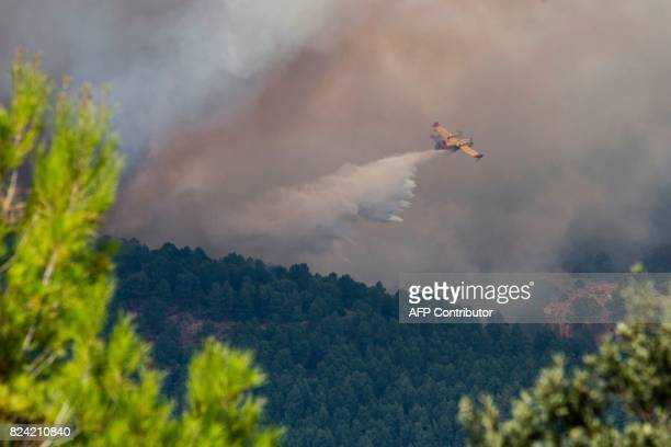 A fire fighting aircraft dumps it's payload over a wildfire near Yeste in south eastern Spain on July 28 2017 Fires ravaged bone dry pine forests and...