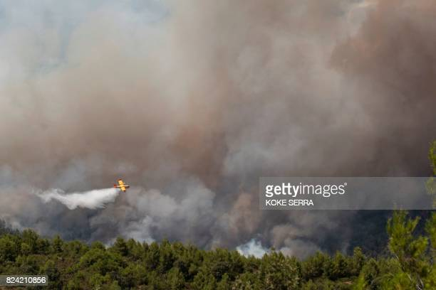 TOPSHOT A fire fighting aircraft dumps it's payload over a wildfire near Yeste in south eastern Spain on July 28 2017 Fires ravaged bone dry pine...
