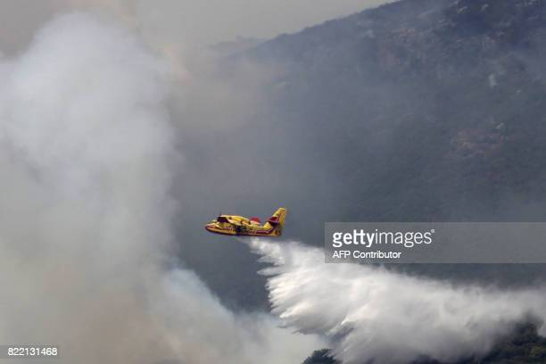 A fire fighting Canadair aircraft drops water over a fire on July 25 in Ortale de Biguglia near Biguglia on the French Mediterranean island of...