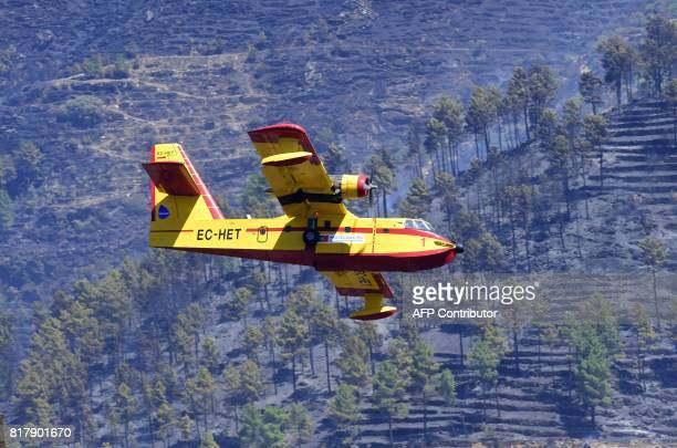 A fire fighting Canadair aircraft flies over scorched hills near the village of Alijo on July 18 2017 during a wildfire A month after the deadliest...