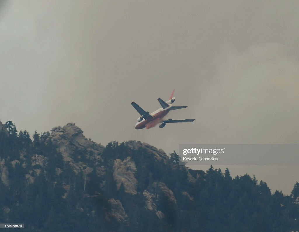 A fire fighting DC-10 plane make a drop on the Mountian Fire on July 18, 2013 near Idyllwild, California. The massive wildfire in Riverside county has grown to 23,000 acres and is advancing towards the mountain town of Idyllwild on one front and city of Palm Springs on the other, destroying several homs and forcing the evacuation of 6,000 people.