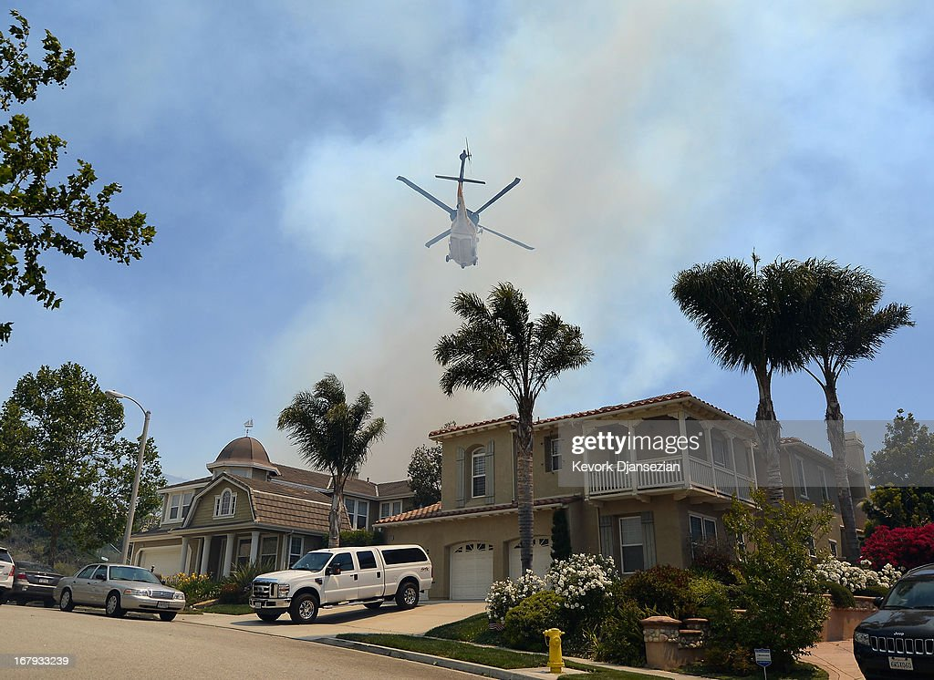 A fire fighting helicopter comes in to make a water drop behind some home threatened by a wildfire on May 2, 2013 in Newbury Park, California. Winds have made fighting the blaze, called the Springs Fire, more difficult and authorities have ordered some mandatory evacuations in the area.