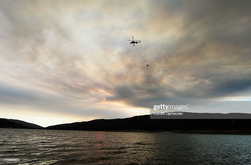 A fire fighting helicopter dips into Lake Hemet to pick up water under the smoke of the Mountain Fire July 18, 2013 near Idyllwild, California. The massive wildfire in Riverside County has grown to 23,000 acres and is advancing toward the mountain town of Idyllwild on one front and city of Palm Springs on the other front destroying several homes and forcing the evacuation of 6,000 people.
