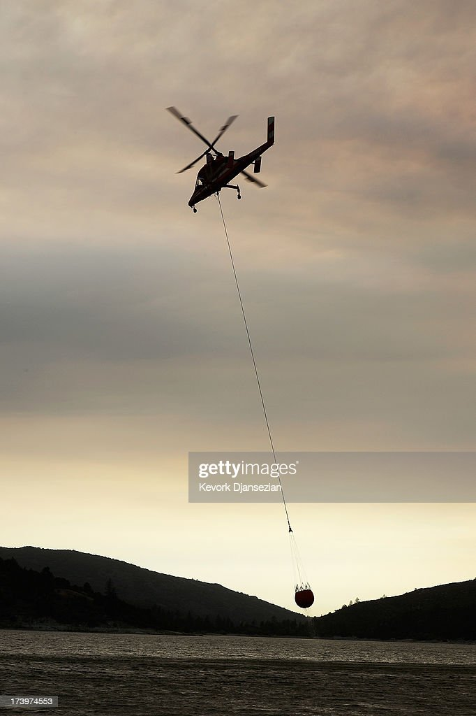 A fire fighting helicopter drops down to pick up water from Lake Hemet to fight the Mountian Fire on July 18, 2013 in Idyllwild, California. The massive wildfire in Riverside county has grown to 23,000 acres and is advancing towards the mountain town of Idyllwild on one front and city of Palm Springs on the other front destroying several homs and forcing the evacuation of 6,000 people.