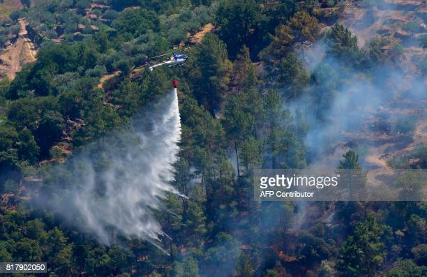 A fire fighting helicopter drops water over a fire near the village of Alijo on July 18 2017 during a wildfire A month after the deadliest forest...
