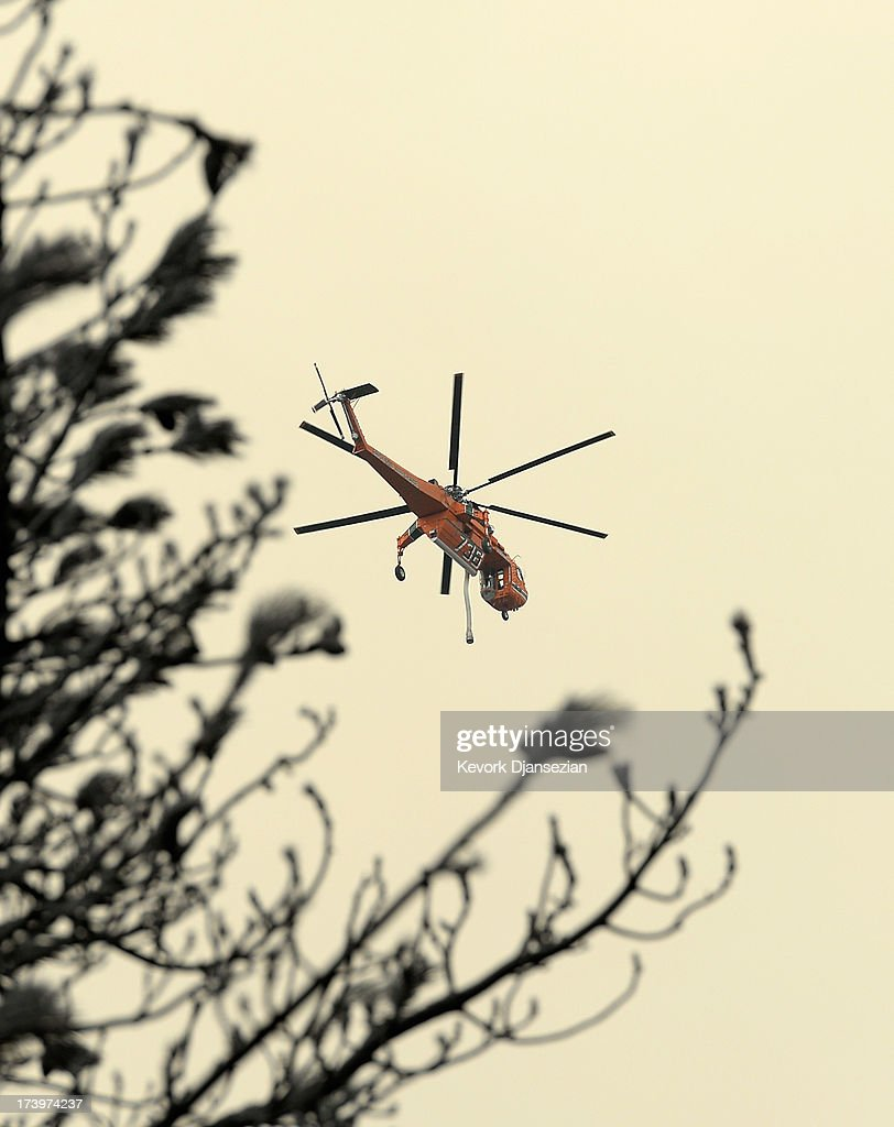 A fire fighting helicopter heads out to fight the Mountian Fire on July 18, 2013 in Idyllwild, California. The massive wildfire in Riverside county has grown to 23,000 acres and is advancing towards the mountain town of Idyllwild on one front and city of Palm Springs on the other front destroying several homs and forcing the evacuation of 6,000 people.