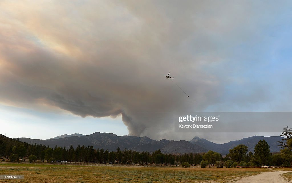 A fire fighting helicopter heads to Lake Hemet to pick up water as a larg plum of smoke rises to the sky from the out to control Mountian Fire on July 18, 2013 in Idyllwild, California. The massive wildfire in Riverside county has grown to 23,000 acres and is advancing towards the mountain town of Idyllwild on one front and city of Palm Springs on the other front destroying several homs and forcing the evacuation of 6,000 people.