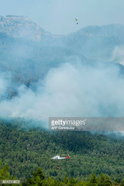 Fire fighting helicopters carry their payload over a wildfire near Yeste in south eastern Spain on July 28 2017 Fires ravaged bone dry pine forests...