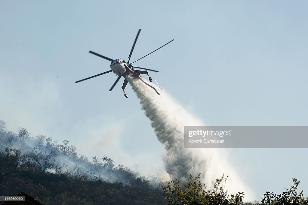 Fire fighting helicopters make water drops onto a hillsdie behind homes threatened by the out of control wildfire on May 2, 2013 in Newbury Park, California. Hundreds of firefighters are battling wind and dry conditions as over 6000 acres have already been burned northwest of Los Angeles.