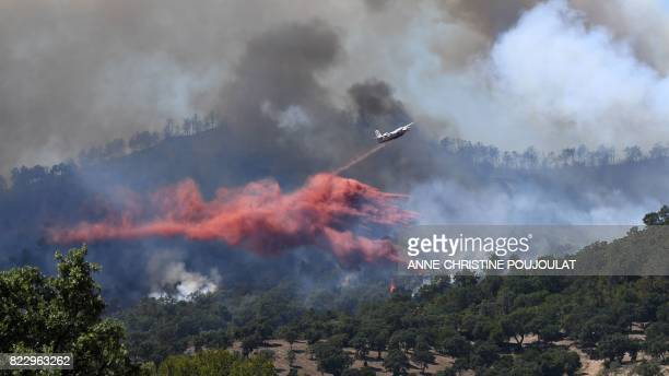 A fire fighting Tracker aircraft drops fire retardant over a fire near BormeslesMimosas southeastern France on July 26 2017 Over 10000 people...
