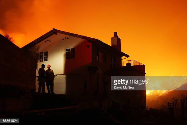 Fire fills a canyon behind a partially burned house on the eastern flank of the Jesusita fire at night on May 8 2009 in the mountains overlooking...