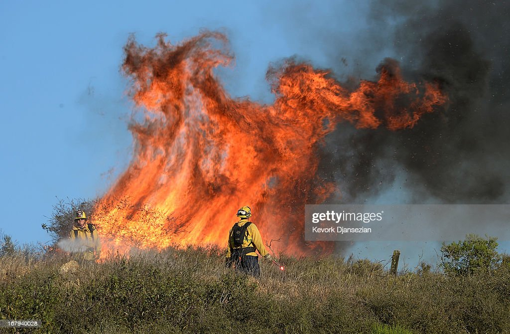 Fire firghters set back fires to burn off dry brush to protect homes behind a hillsdie threatened by an out of control wildfire on May 2, 2013 in Newbury Park, California. Hundreds of firefighters are battling wind and dry conditions as over 6000 acres have already been burned northwest of Los Angeles.