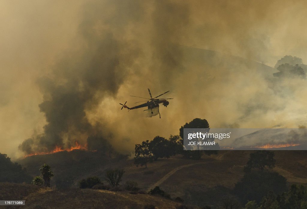 A fire helicopter dumps water on a brush fire near Highway 101 and Calabasas on August 18 2013 north of Los Angeles California A car fire sparked a...