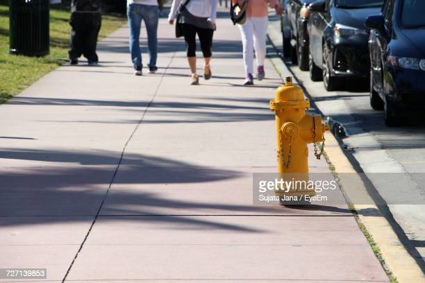 Fire Hydrant On Footpath With Low Section Of People Walking In Background