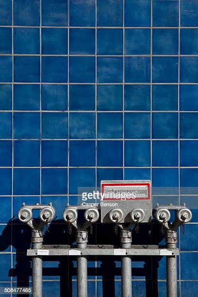 Fire hydrants against blue tiled wall