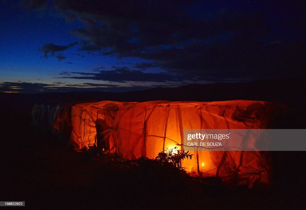 A fire illuminates a Maasai hut at Mount Suswa in Kenya on December 20, 2012. Mount Suswa is a sacred place for the Maasai tribe and every 10 years Maasai from all over Kenya gather to witness the coming of age ceremony for the Morans known as an 'Age Set'. The 'age set' sees Morans achieving the status of manhood in their communities' eyes. Before this coming of age ceremony Morans must traditionally be circumcised and spend up to 4 years in the wilderness with a group of around 10 or less to fend for themselves and put into practice hunting techniques and life skills passed on by their elders. AFP PHOTO / Carl de Souza